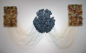 """The Stream of Consciousness"" 2008, linen threads, dyed and covered with wax, stitched on the fabric on one side, and tied with rusted razor blades on the other. Three hundred razor blades are connected to the disc magnets suspended away from the wall, 4' H x 10'W x 1' D"